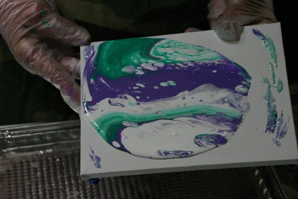 Tilting purple green and white paint on acrylic pour canvas